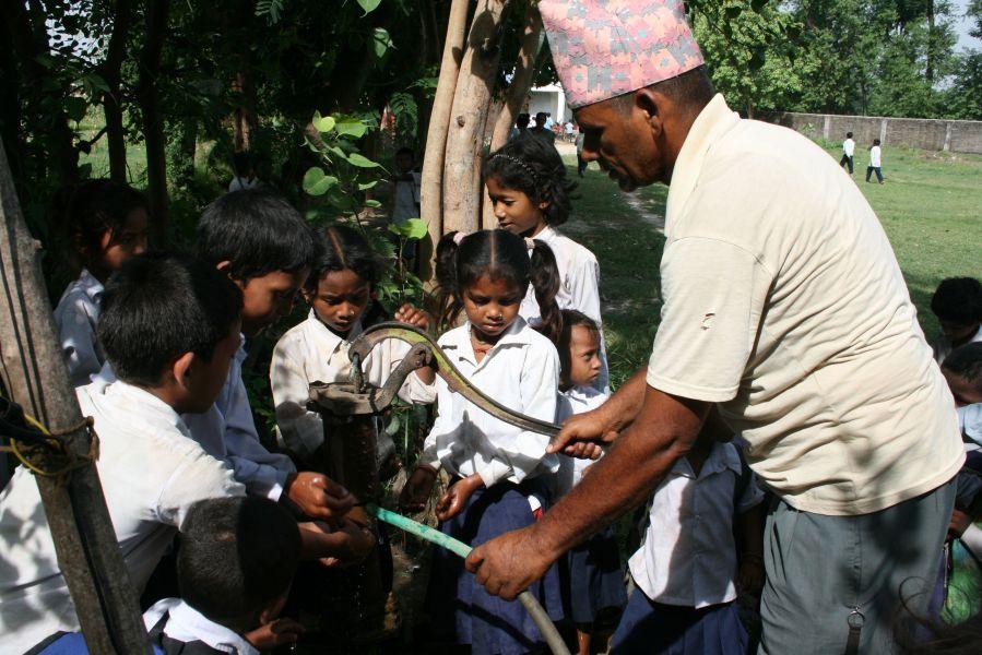 Pedellen Raju hjælper børnene med at få vasket hænder