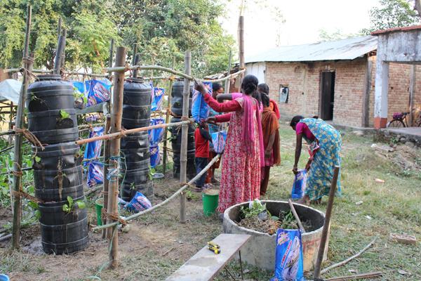 Efter havemanden Raju Basals ide, lavede vi også et stakit foran tønderne sådan at vi kunne lægge plastik-dug over for at beskytte mod sol og regn.